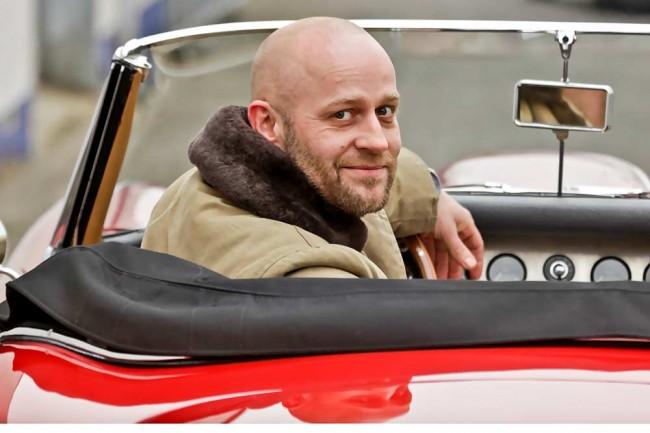 Der Schauspieler mit seiner großen Liebe: Kein anderes Auto hat Jürgen Vogel schon von Kindesbeinen an so fasziniert wie der Jaguar E-Type. Da geht es ihm wie unzähligen anderen Männern auf dieser Welt: Die Formen sind unerreicht, das Image könnte kaum sportlicher sein. Aber da Vogel an bestimmten Drehorten pünklich ankommen muss, kann er sich nicht auf eine automobile Diva verlassen. Die fährt er dafür, wenn er an Events wie Gleichmäßigkeitsrallyes teilnimmt