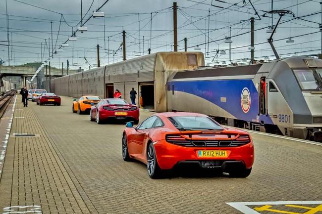 Spannende Reise mit fünf McLaren MP4-12C unter dem Kanal hindurch: Der Start in Woking geschieht bei englischem Regenwetter, das Einfädeln in den Zug ist durchaus ungewöhnlich. Wegen der geringen Bodenfreiheit dürfen die Autos auf die Lastwagenebene und müssen nicht über eine Rampe in den ersten Stock fahren